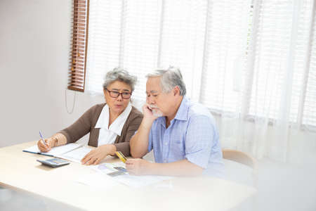 Asian senior couple serious worried with calculating bills to pay per month or debt, Retired elderly reading loan document, Money problems concept