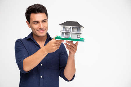 Handsome young Caucasian man inspector holding single home, Home inspection service before transferring to house owner concept