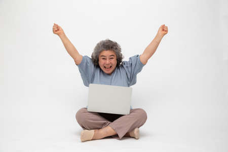 Excited senior asian woman feeling winner celebrating victory online business success and sitting on floor with laptop isolated on white background, Freelance mature concept