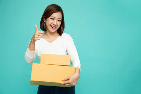 Happy Asian woman holding package parcel box and thumb up isolated on green color background, Delivery courier and shipping service concept Фото со стока