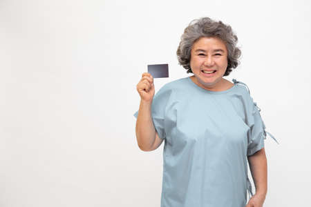 Asian senior woman patient showing health insurance isolated on white background.