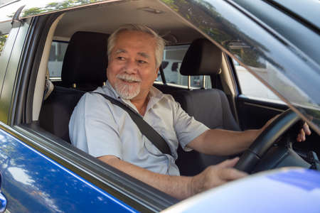 Asian senior men driving a car and smile happily with glad positive expression during the drive to travel journey, People enjoy laughing transport and relaxed happy mature man on roadtrip concept