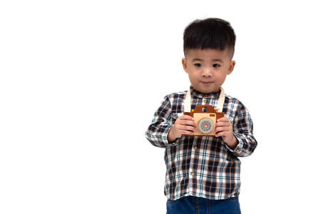 Attractive Asian little boy photographer wearing striped shirt standing isolated over white background, Taking a picture with toy photo camera, Two year one month old Stockfoto