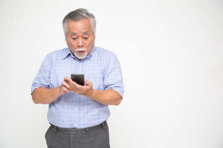 Asian senior man using smartphone and receiving good news from the message on mobile chat application over white background, Wow and surprised concept