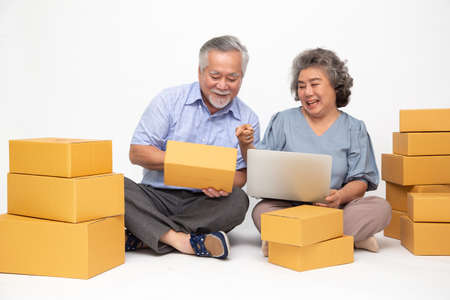 Asian senior couple startup small business freelance with parcel box and computer laptop and sitting on floor isolated on white background, Online marketing packing box delivery concept