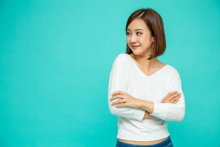 Happy young casual asian woman hugging herself isolated on green background. Love yourself concept