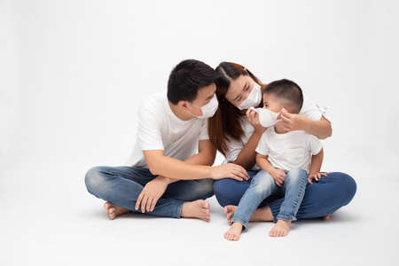 Asian family wearing protective medical mask for prevent virus Wuhan Covid-19 and sitting together on floor isolated white background. Family protection from contaminated air concept Banque d'images