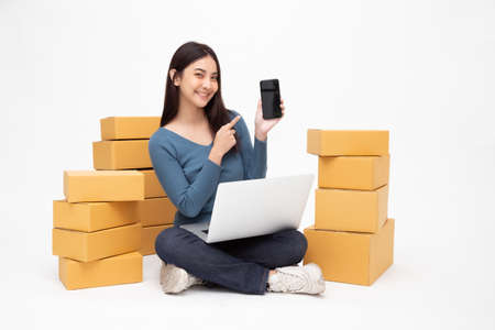 Young asian woman startup small business freelance holding parcel box, mobile phone and computer laptop and sitting on floor isolated on white background, Online marketing packing box delivery concept