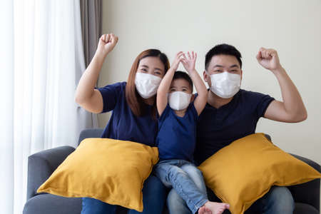 Asian family wearing protective medical mask for prevent virus Covid-19 and hand up and sitting together in living room. Family protection from contaminated air concept Reklamní fotografie