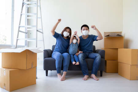 Asian family wearing protective medical mask for prevent virus covid-19 and hand up during moving day and relocating at new home. Moving house and new real estate concept