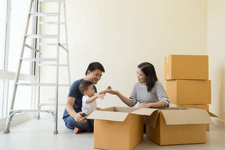Happy Asian family with cardboard boxes in new house at moving day, Real estate and home concept