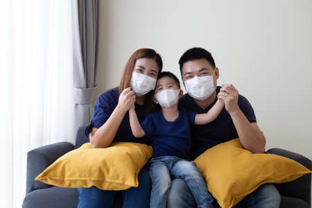 Asian family wearing protective medical mask for prevent virus Covid-19 and hand up and sitting together in living room. Family protection from contaminated air concept Standard-Bild