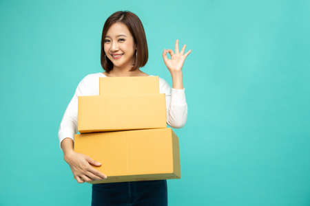 Happy Asian woman holding package parcel box and and showing ok, Delivery courier and shipping service concept