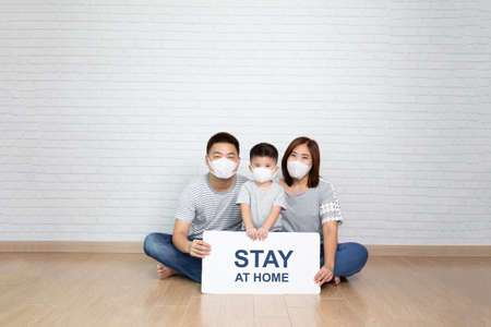 Asian family wearing protective medical mask for prevent virus Covid-19 holding white paper with stay at home on hand and sitting together on floor at home