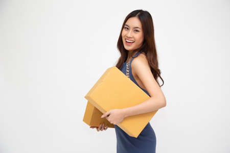 Happy Asian woman holding package parcel box isolated on white background, Delivery courier and shipment service concept