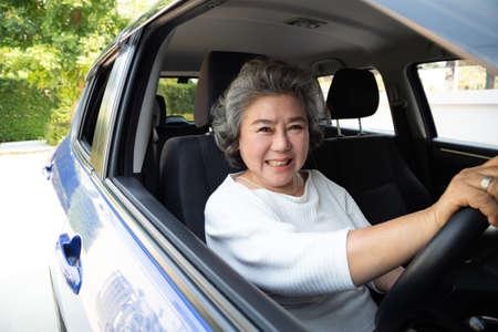 Femme âgée asiatique conduisant une voiture et souriant joyeusement avec une expression positive joyeuse pendant le trajet en voiture, les gens apprécient le transport en riant et le concept de conduite