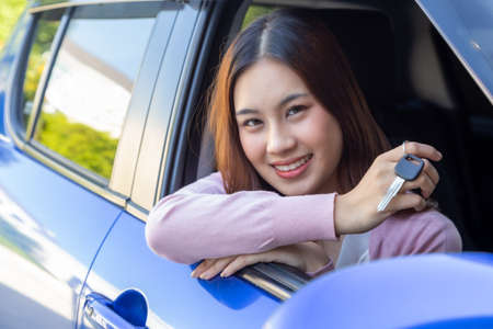 Asian woman driver smiling and showing new car keys and sitting inside the car