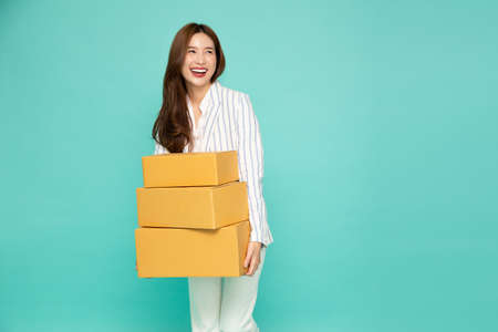 Happy Asian woman holding package parcel box isolated on light green background, Delivery courier and shipping service concept