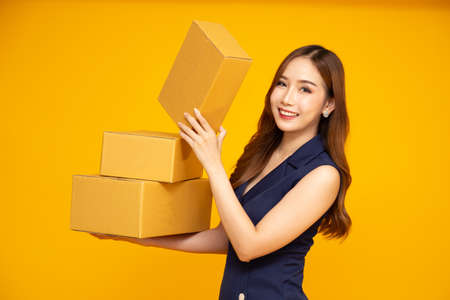 Happy Asian woman smiling and holding package parcel box isolated on yellow background, Delivery courier and shipping service concept