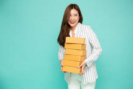 Happy Asian woman smiling and holding package parcel box isolated on light green background, Delivery courier and shipping service concept Фото со стока