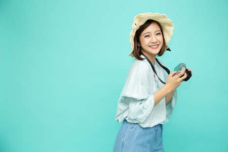 Portrait of asian woman tourist holding digital camera isolated on green background