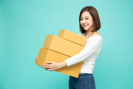 Happy Asian woman holding package parcel box, Delivery courier and shipment service concept 免版税图像