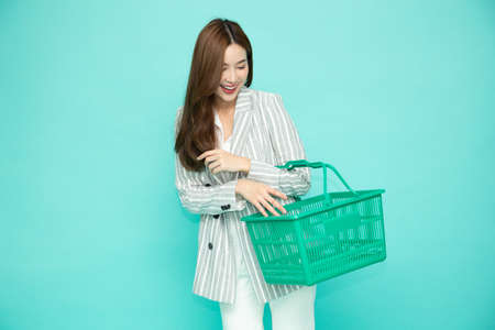 Beautiful Asian woman smiling and holding shopping basket isolated on light green background