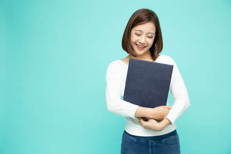 Young beautiful Asian woman smiling and holding document file isolated on green background 免版税图像