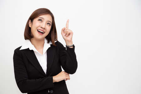 Smiling asian business woman pointing up isolated over white background 免版税图像