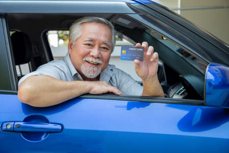 Asian senior man sitting in car and holding credit card