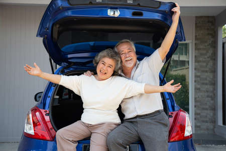 Happy Asian senior couple standing back of the car and enjoying journey trip, Mature travel lifestyle during retirement concept 免版税图像