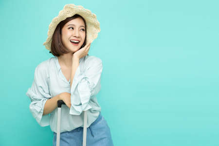 Beautiful young asian woman with suitcase isolated on green background, Vacation journey and travel concept 免版税图像