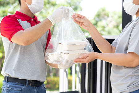Asian deliverman wearing face mask holding plastic bag with food box delivery to woman customer 免版税图像