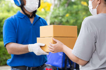 Asian delivery man wearing face mask and blue uniform with motorcycle delivering parcel box express service to woman customer