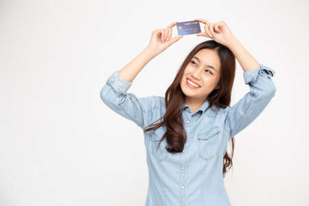 Portrait of a happy young woman holding atm or debit or credit card and using for online shopping spending a lot of money isolated over white background, Asian female model