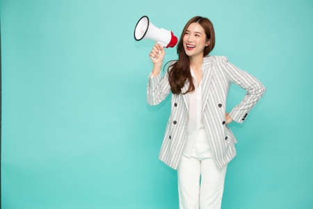 Asian business woman holding megaphone isolated on light green background, Speech and announce concept 免版税图像