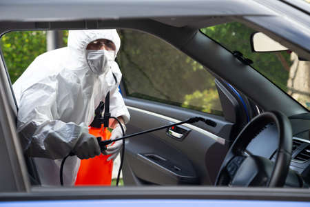 Virologist man wearing PPE kits kills bacteria and viruses inside the car, COVID-19 sterilization and cleaning service in the car concept