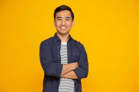 Portrait of asian man with arms crossed and smile isolated over yellow background, Looking at camera, Happy feeling concept