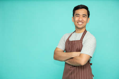 Portrait of Asian workers fresh market with brown apron standing with arms crossed isolated on green background 免版税图像