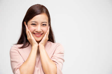 Portrait of excited screaming young asian woman standing in pink dress isolated over white background, Wow and surprised concept 免版税图像