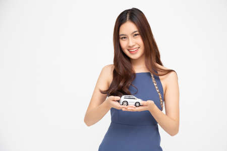 Asian woman holding car model isolated on white background, Travel Insurance concept 免版税图像