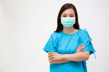 Young Asian woman wearing patient outfits with arms crossed and wearing face mask isolated on white background