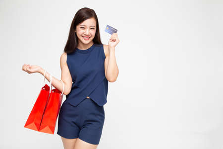 Portrait of a happy young women holding shopping bags and credit card isolated over white background, Year end sale or mid year sale promotion clearance for Shopaholic concept, Asian female model