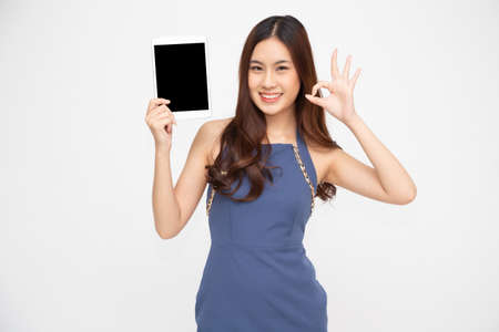 Happy asian woman holding tablet and ok sign isolated on white background