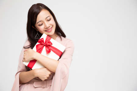 Happy beautiful asian woman smile and hugging gift box isolated on white background. Teenage girls in love, Receiving gifts from lovers. New Year, Christmas and Valentines Day concept 免版税图像