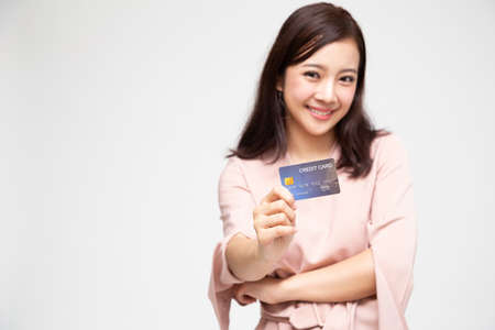 Portrait of a happy Asian woman holding atm or debit or credit card and using for online shopping spending a lot of money isolated over white background, Asian female model, Focus hand concept