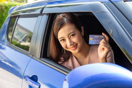Happy young Asian woman holding payment card or credit card and sitting in car