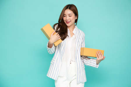 Happy Asian woman smiling and holding package parcel box isolated on light green background, Delivery courier and shipping service concept 免版税图像