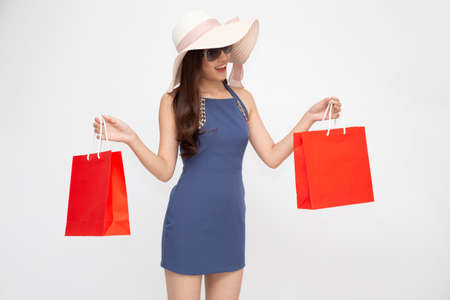 Young Asian woman holding red shopping bags isolated on white background