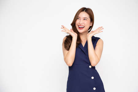Portrait of excited screaming young asian woman standing in blue dress isolated over white background, Wow and surprised concept 免版税图像